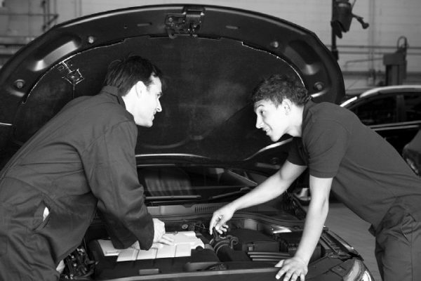 two men over car engine