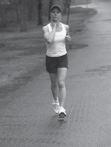 woman running and taking her pulse