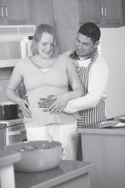 man with hand on pregnant woman's belly