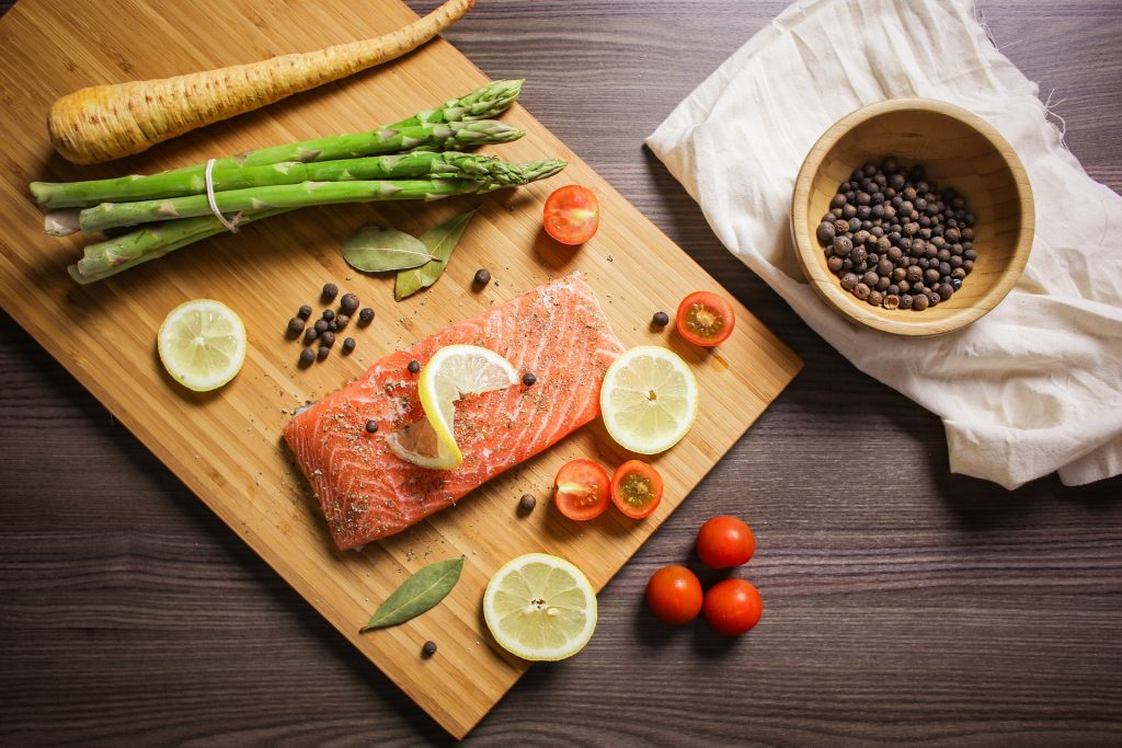 raw fish and vegetables on cutting board