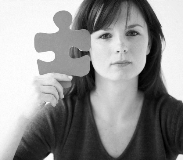 woman holding a large puzzle piece