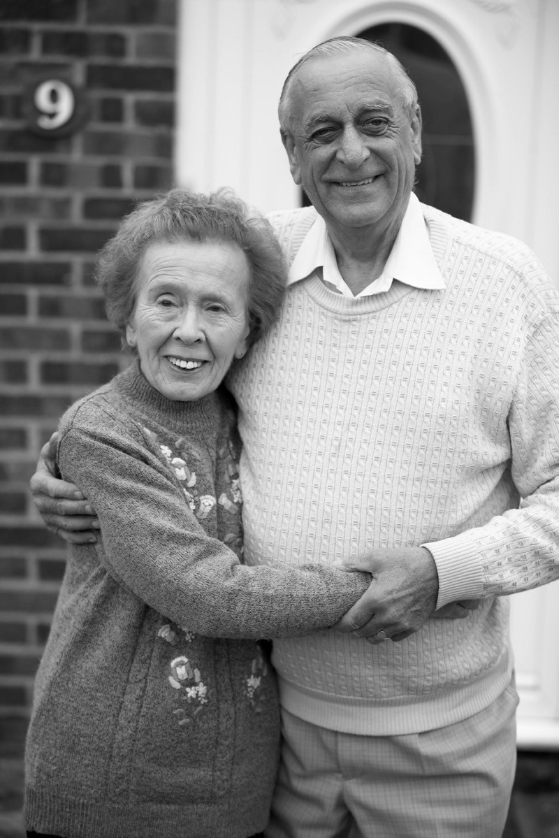 Elderly couple holding one another
