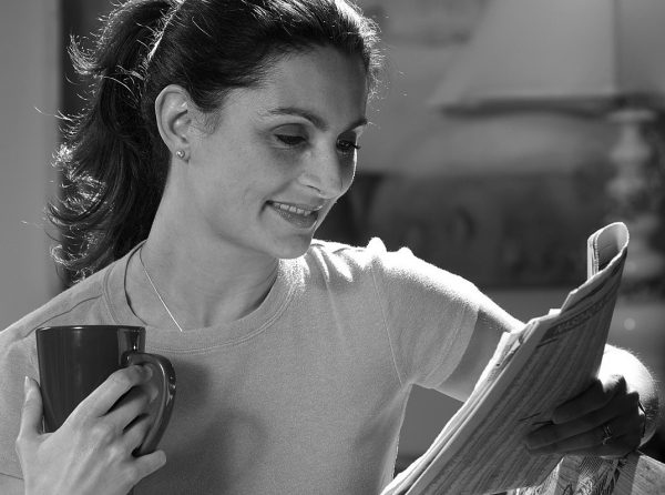 woman drinking coffee, reading newspaper